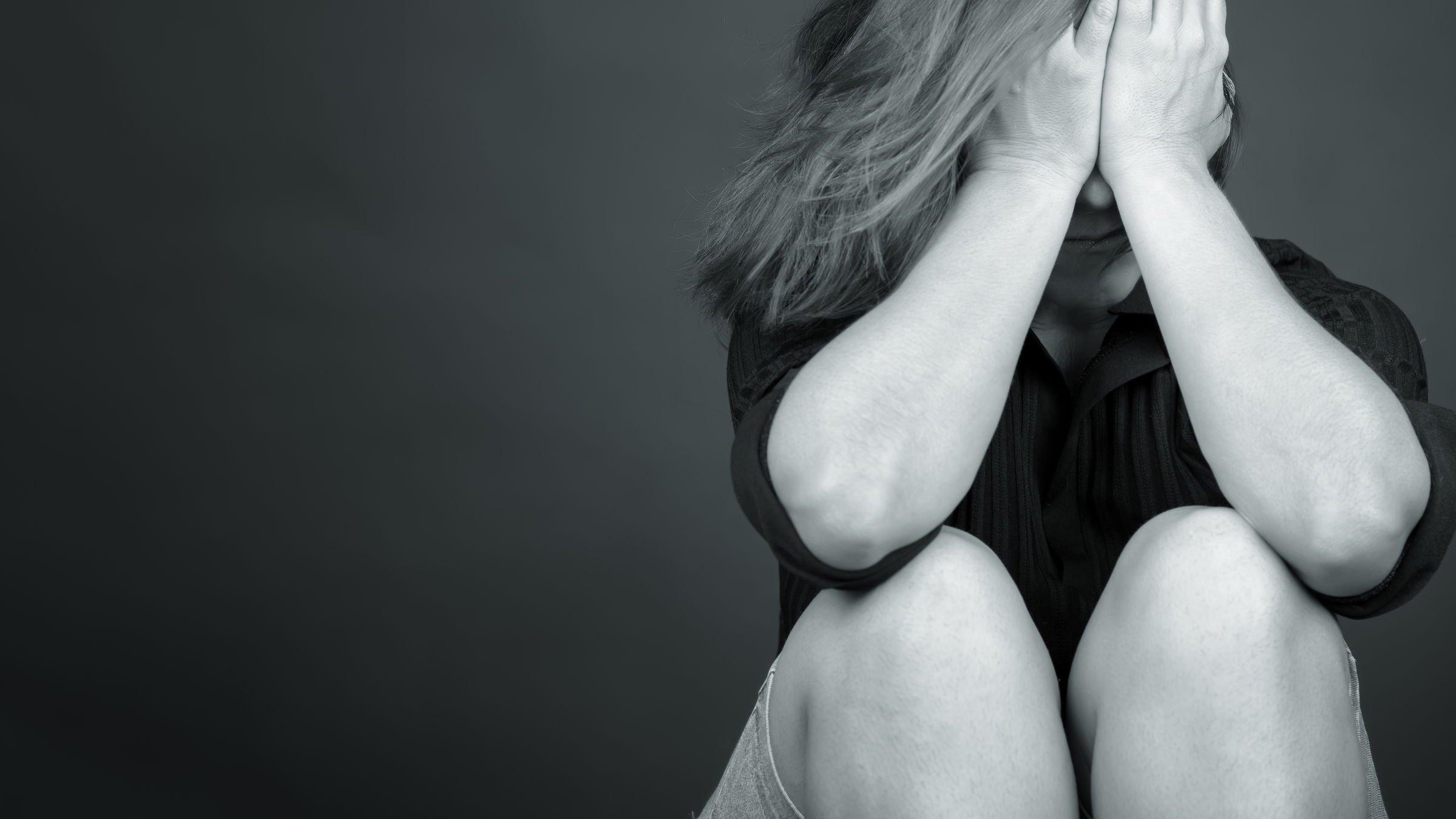 Mulher sentada no chão com as mãos em seu rosto