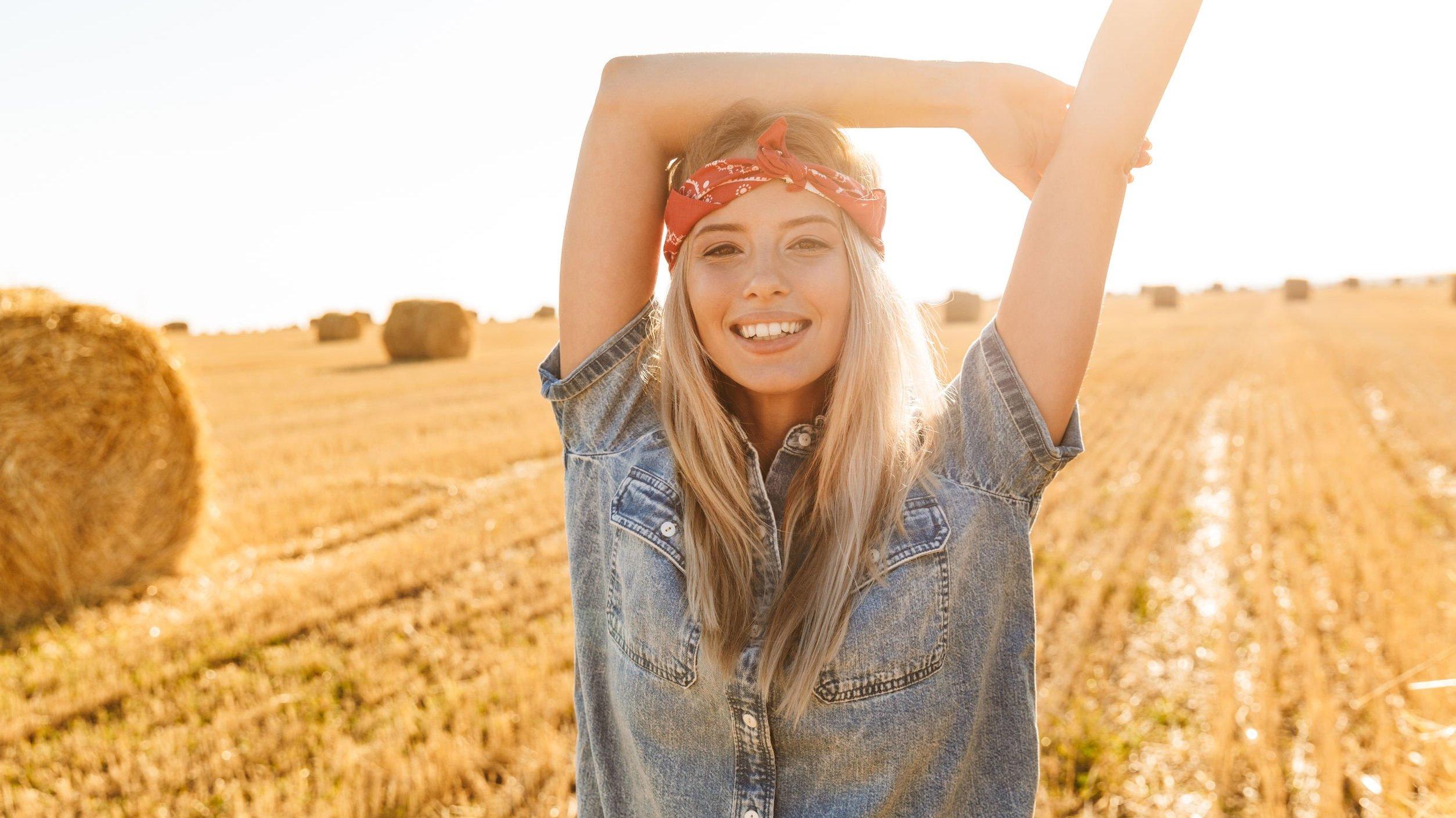 Mulher sorrindo com seus braços levantados em um campo de feno