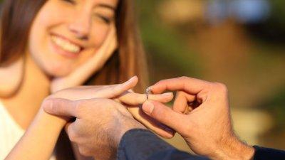 Homem colocando anel em mão de mulher