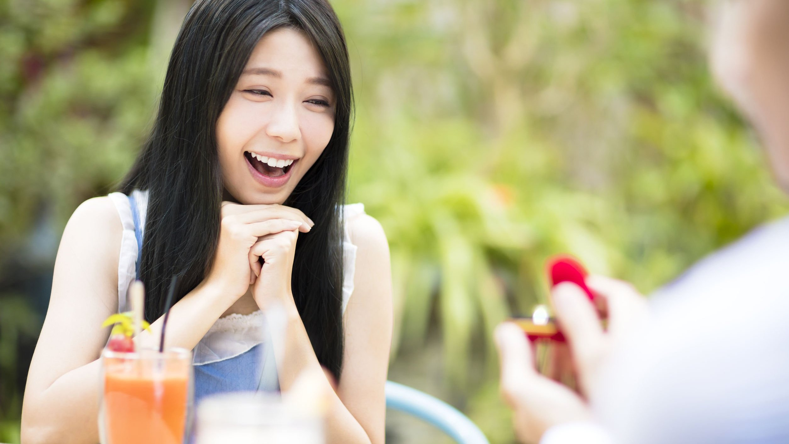 Mulher com a boca aberta, impressionada, olhando para um homem segurando uma caixa vermelha com um anel.