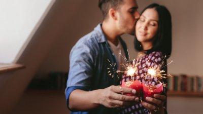 Casal com chapéu de aniversário e língua de sogra na boca sorrindo