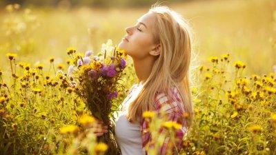 Mulher de perfil segurando buquê de flores em campo com flores amarelas iluminada pelo sol