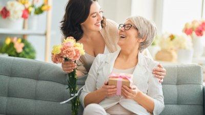 Filha beijando rosto da mãe feliz