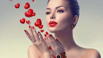 Mulher com as mãos esticadas para frente, com as palmas viradas para cima, soprando-as. Delas, saem desenhos de corações flutuando.