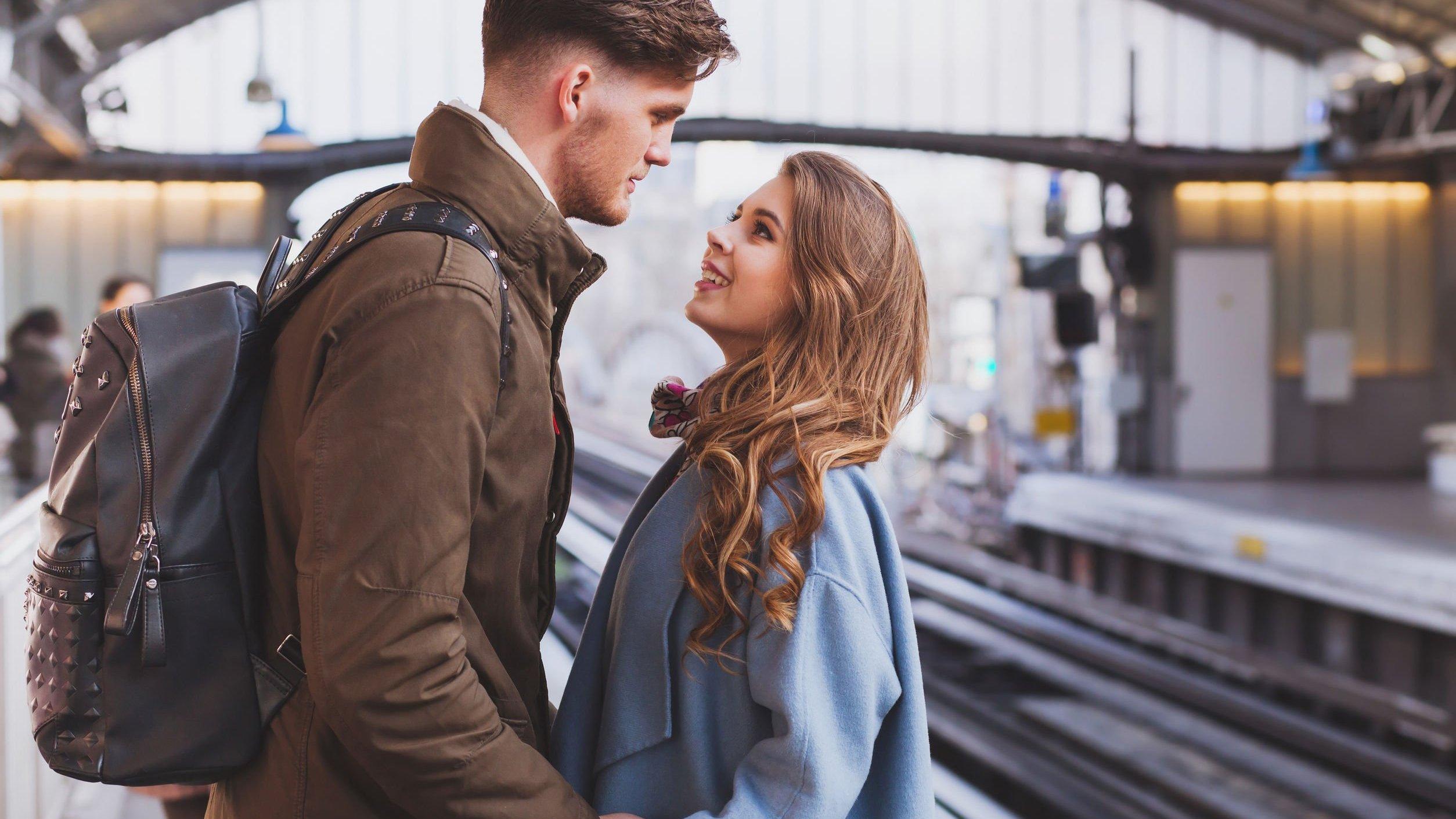 Homem e mulher em estação de trem, olhando um para o outro.