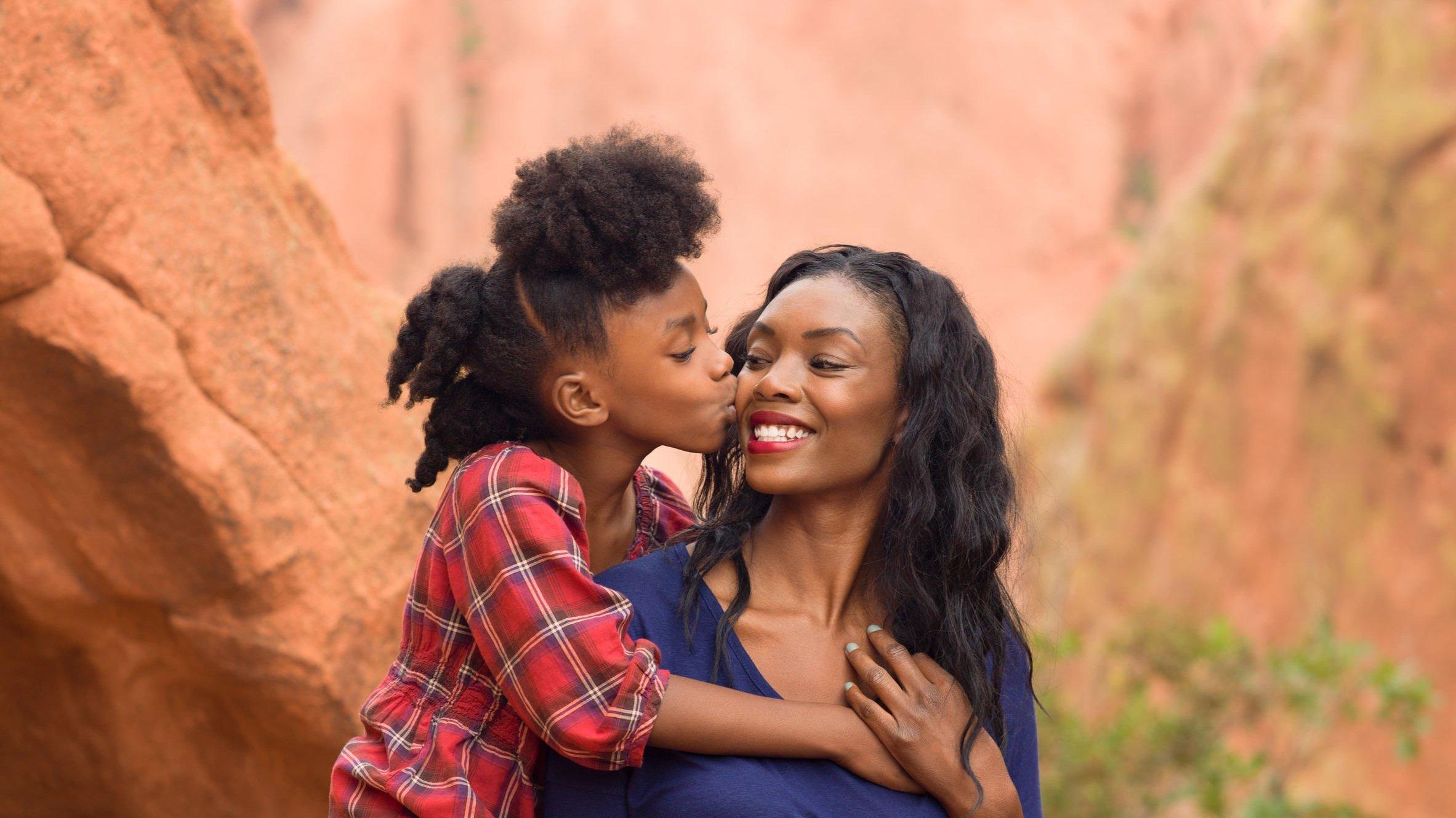 Filha beijando rosto de sua mãe