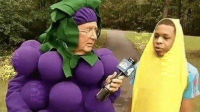 Repórter vestindo fantasia de uva entrevistando menino que veste uma fantasia de banana.