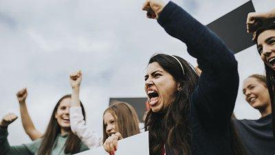 Mulheres protestando segurando cartazes e ergendo seus punhos para o alto.