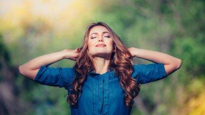 Mulher com mãos atrás da cabeça e cabeça para o alto com sol refletindo de olhos fechados