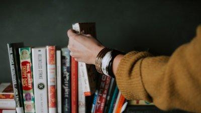 Mão pegando livro em prateleira de livros