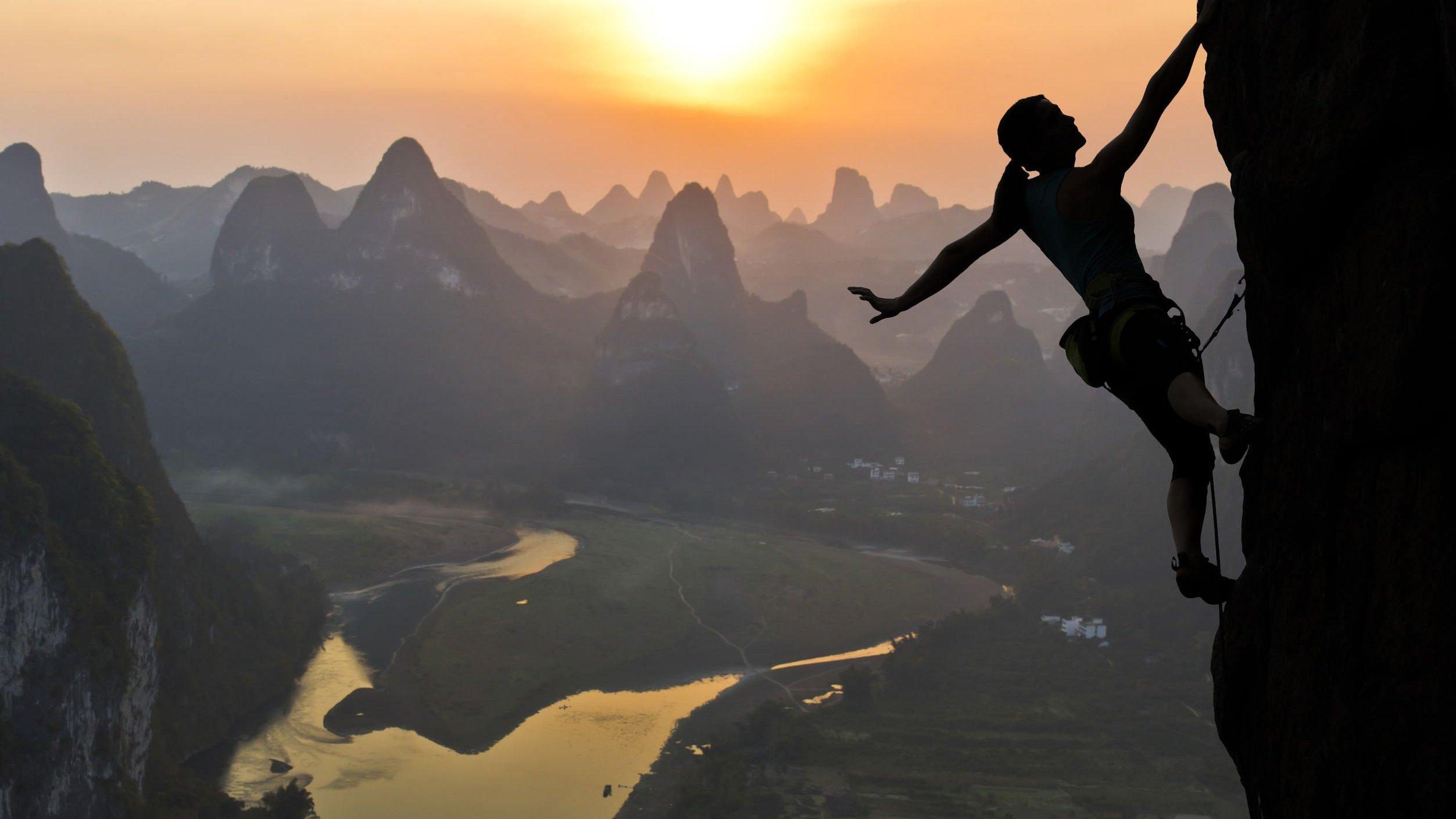 Silhueta de mulher escalando montanha no pôr-do-sol.