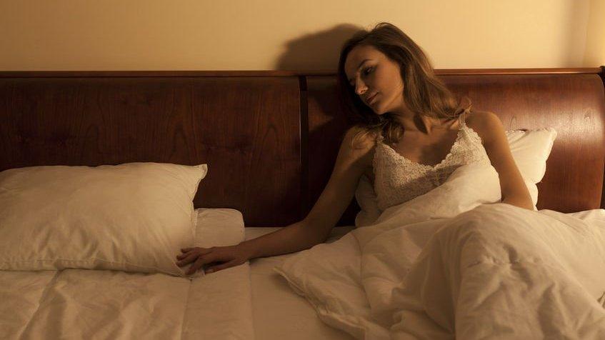 Mulher jovem na cama sofrendo por um amor não correspondido