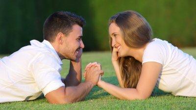 Casal abraçado com rapaz beijando rosto de mulher sorrindo ambos de óculos de sol