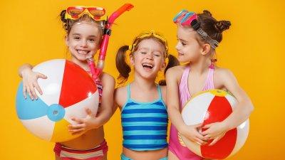 Meninas brancas com trajes de banho e expressões sorridentes