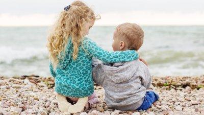 Duas crianças pequenas abraçadas em frente ao mar