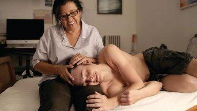 Protagonista do colo, sentada, com outro personagem deitado em seu colo, enquanto ela faz carinho em sua cabeça.