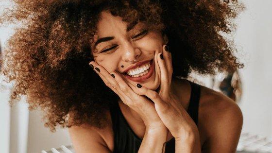 Mulher sorrindo de olhos fechados com as mãos no rosto