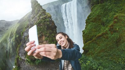 Mulher fazendo selfie com cachoeira ao fundo