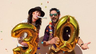 Homem e mulher segurando balão dos números três e zero, comemorando e sorrindo