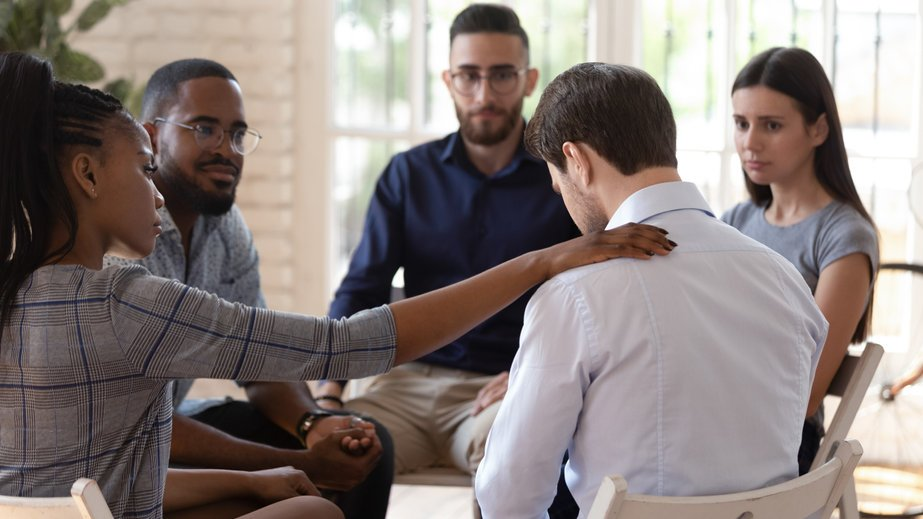 Duas meninas se abraçando próximas a um lago.