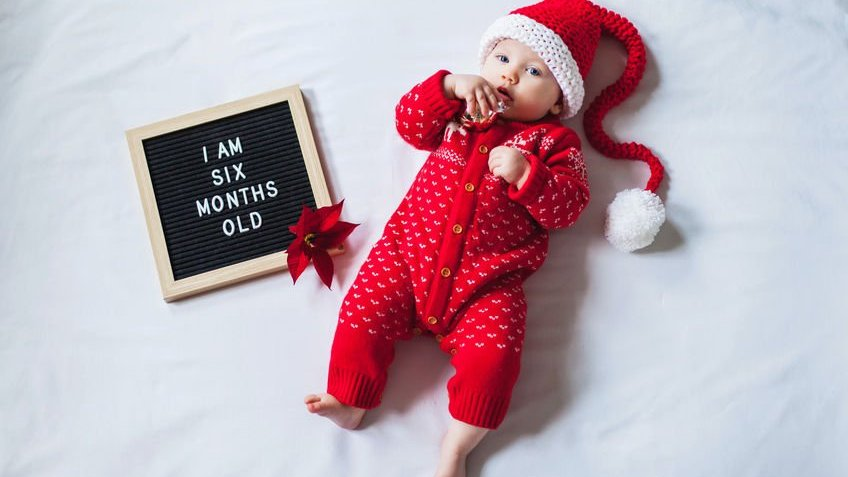 Bebê com roupas natalinas e placa ao lado com os dizeres tenho seis meses de idade