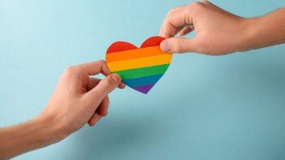 Pessoas segurando coração estampado com a bandeira do arco-íris