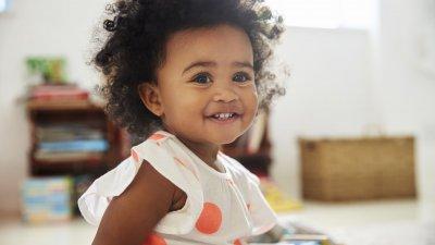 Bebê sentado no chão sorrindo