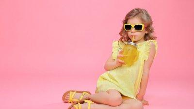 Menina deitada e tomando suco