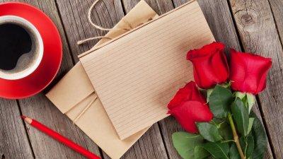 Papeis de carta ao lado de um buquê de rosas e uma xícara de café.