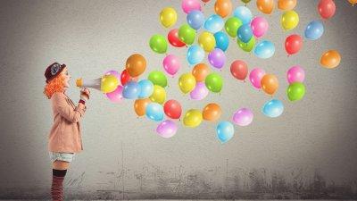 Mulher vestida de palhaço, falando num megafone com balões coloridos.