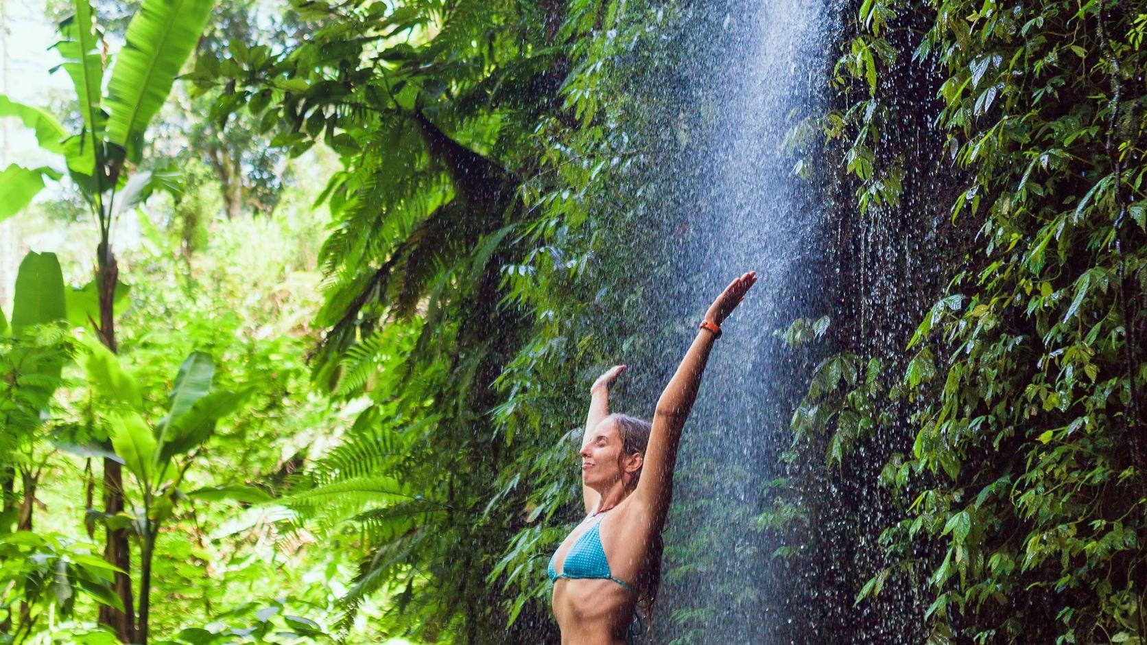 Mulher de braços erguidos sob cachoeira