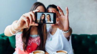 Duas mulheres tirando selfie com celular
