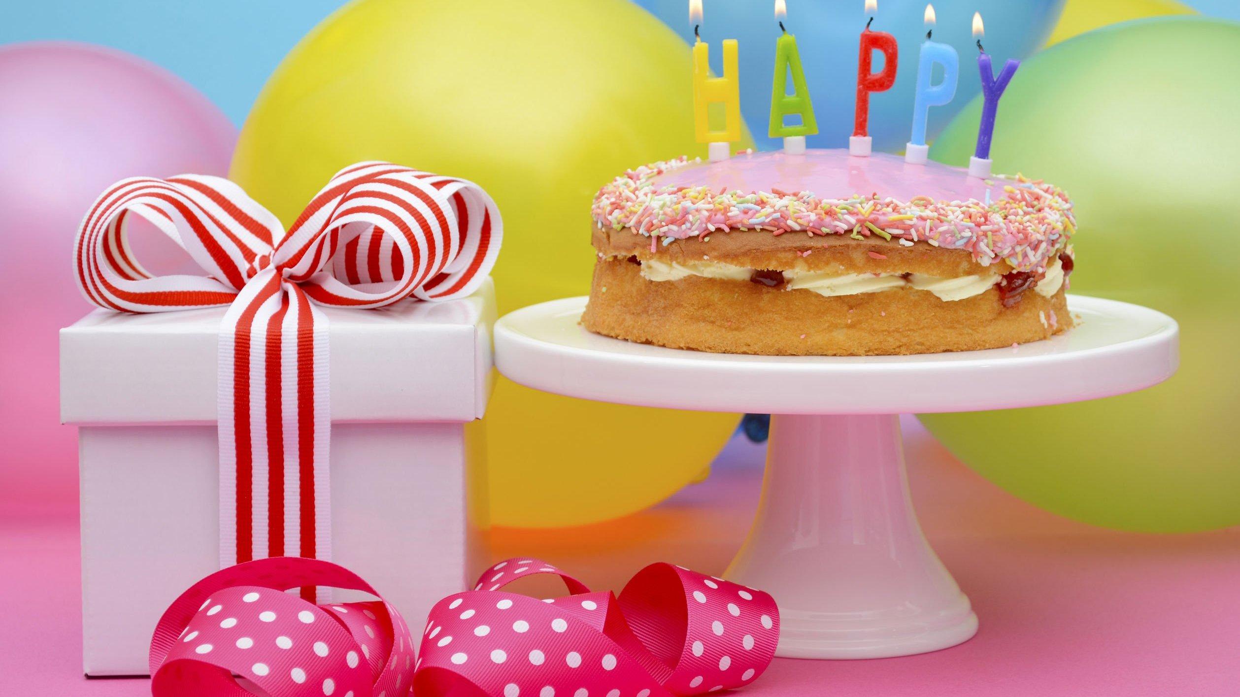 Bolo de aniversário com balões coloridos ao fundo e caixa de presente ao lado.