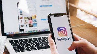 Mulher segurando plaquinhas com o símbolo do Instagram, e outra com o símbolo de coração de curtida no Instagram.