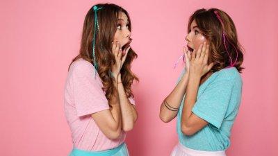Garotas se olhando com rosto de surpresa com roupas rosa e verde invertidas e fundo rosa e verde