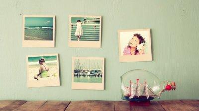 Parede atrás de bancada com pequenas fotos coladas. Em cima da bancada, uma garrafa com um navio dentro.