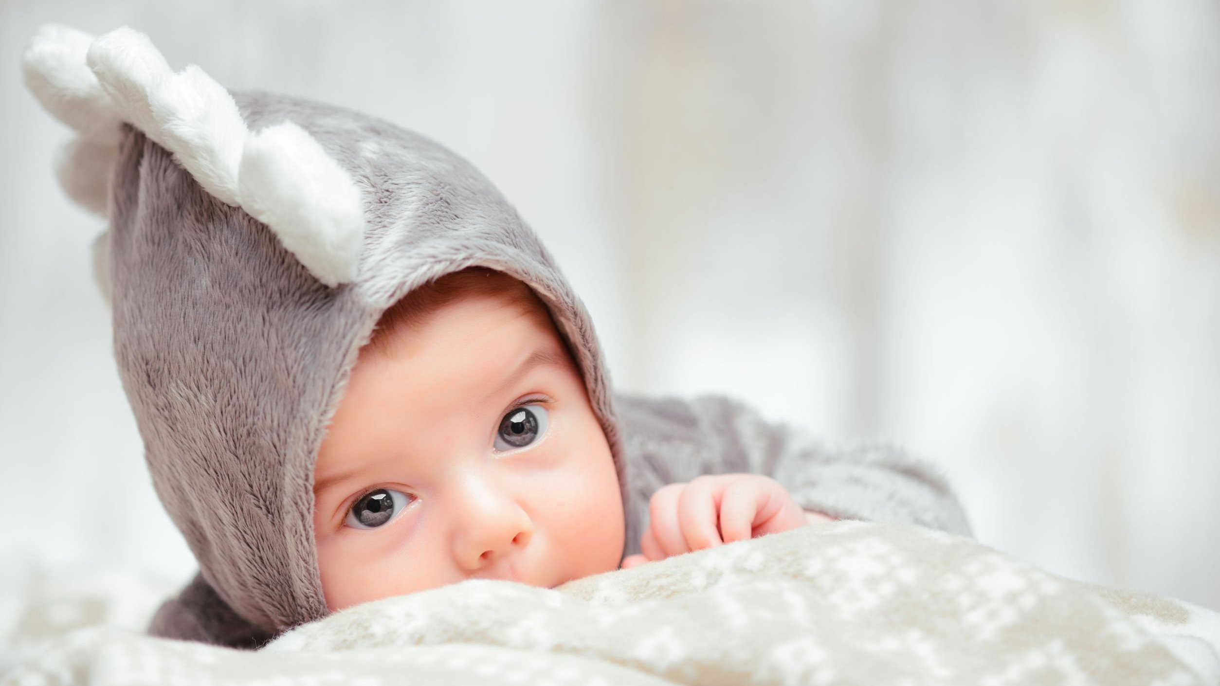 Bebê usando roupinha de dinossauro deitado na cama