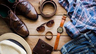 Acessórios masculinos como cinto, óculos escuro, relógio de pulso, sapatos, carteira e uma camisa.