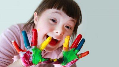 Garota com Síndrome de Down de mãos sujas de tintas coloridas sorrindo