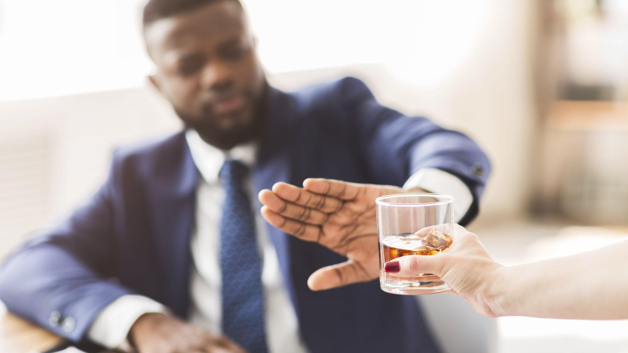 Homem esticando a mão para rejeitar copo com uísque.