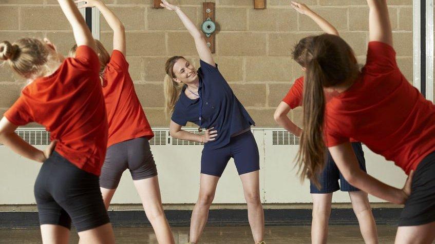 Mulher loira de blusa azul se alongando, enquanto crianças usando blusas vermelhas copiam os movimentos de alongamento