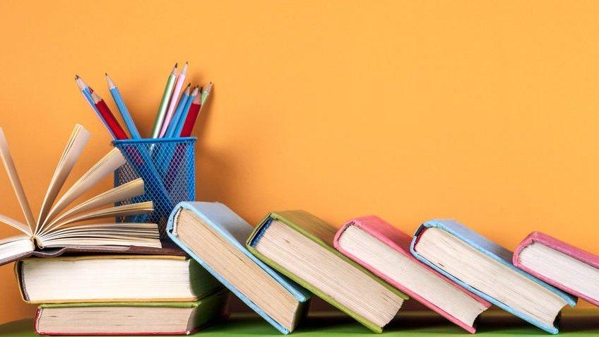 Livros didáticos e porta-canetas com lápis