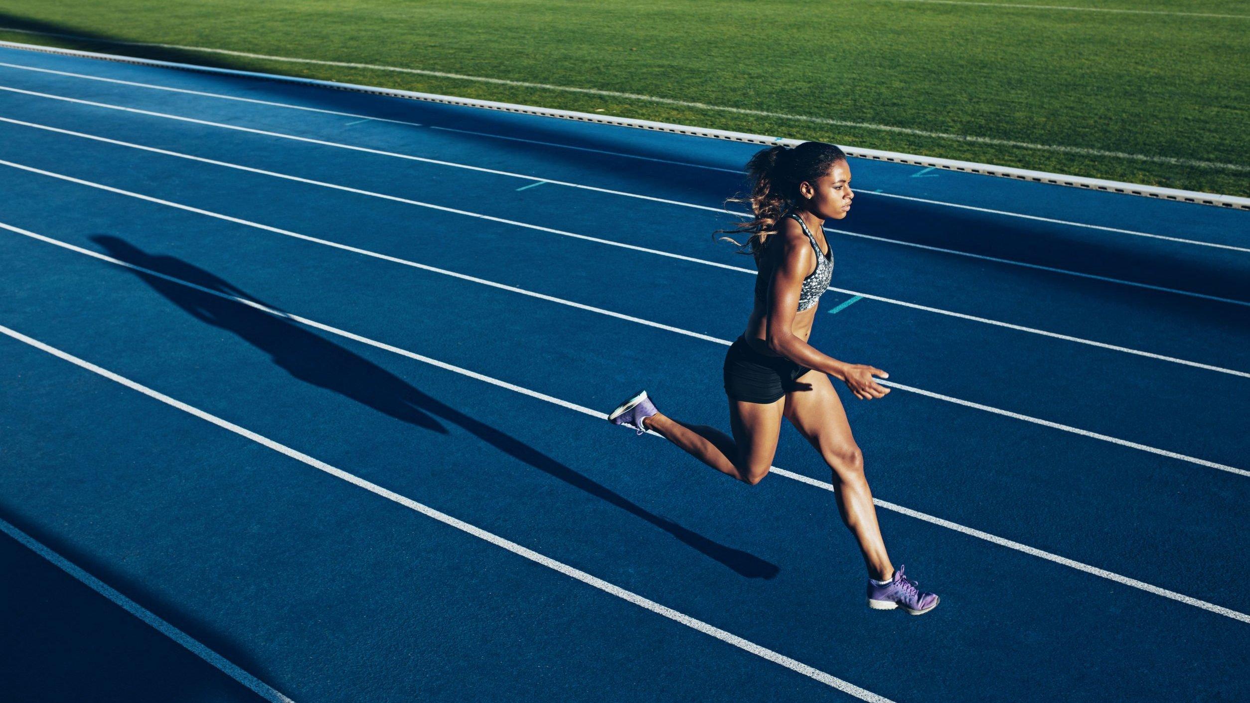Mulher atleta correndo em pista de de corrida.