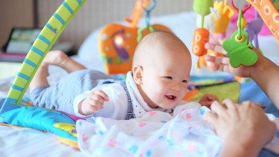 Bebê deitado de bruços na cama, rindo e brincando