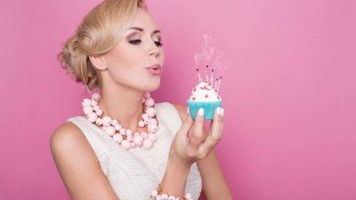 Mulher assoprando as velinhas de um cupcake
