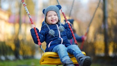 Criança menina com roupas de frio sorrindo enquanto brinca em um balanço