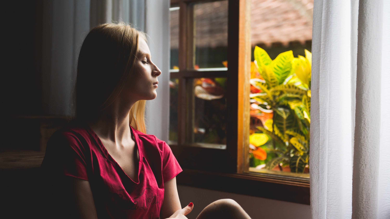 Mulher sentada em frente à janela, com os olhos fechados.
