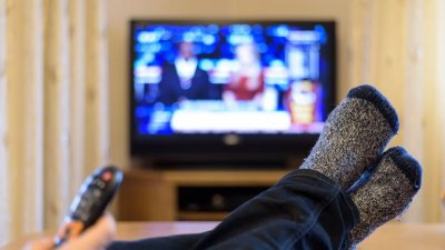 Pés apoiados em com mão mudando canal de TV e TV ao fundo