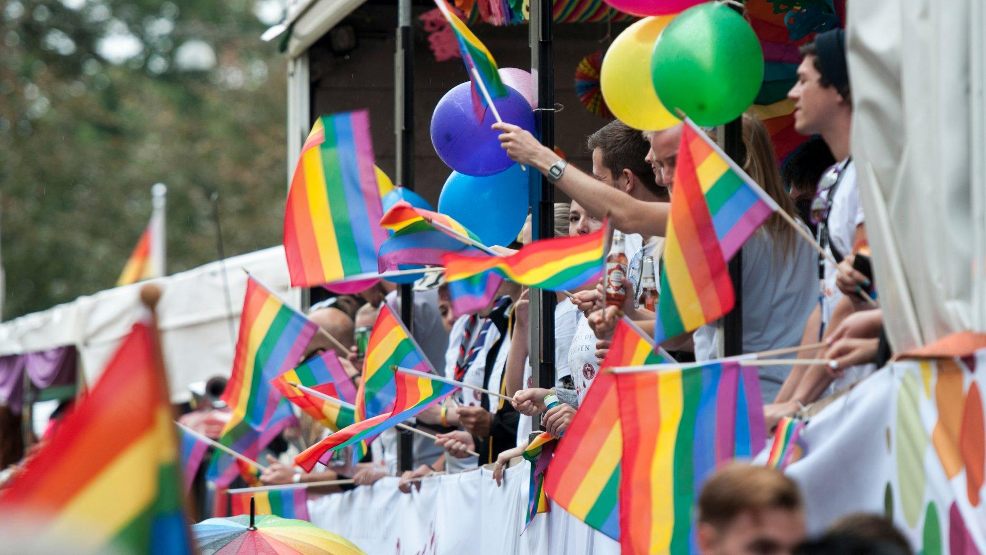 Pessoas com a Pride Flag durante a Parada Gay