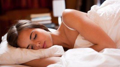 Mulher deitada de lado em cama, dormindo, abraçada em um travesseiro.
